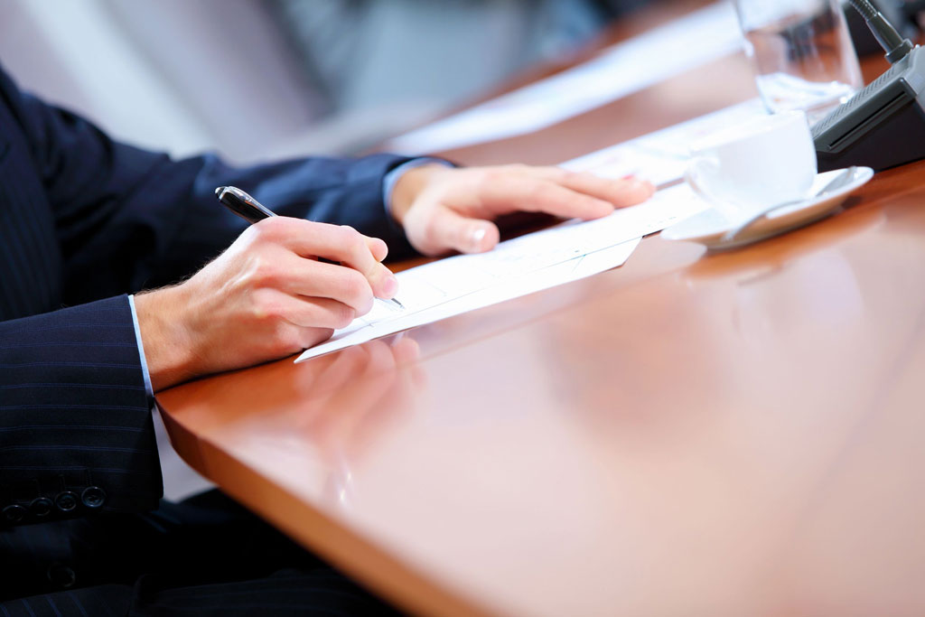 A person in a suit signing a document